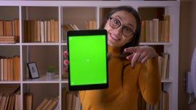 Le portrait du professeur joyeux de brune en verres montre l'?cran vert de chroma du comprim? dans la cam?ra ? la biblioth?que banque de vidéos