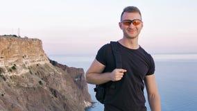 Le portrait du randonneur de sourire de sports caucasiens soulève son sac se tenant sur la falaise au coucher du soleil banque de vidéos