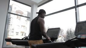 Le portrait du sportif afro-américain qui finit ses exersices sur la voie de course dans le gymnase moderne banque de vidéos
