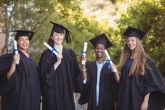 Le portrait du troisième cycle d'université badine la position avec le rouleau de degré dans le campus Photo libre de droits