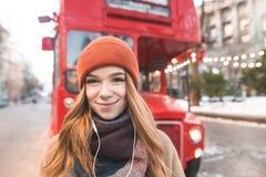 Le portrait en gros plan d'une fille positive dans des écouteurs regarde la caméra au dos d'un autobus rouge Fille de sourire mig photographie stock