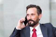 Le portrait en gros plan de l'homme d'affaires sûr s'est habillé dans le costume parlant au téléphone portable d'isolement au-des image libre de droits