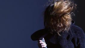 Le portrait en gros plan de la femme soufflant sèche ses cheveux courts au fond bleu banque de vidéos