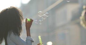 Le portrait en gros plan de la fille afro-américaine de sourire de charme avec les cheveux bouclés soufflant les bulles de savon  clips vidéos