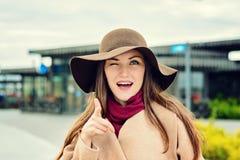 Le portrait en gros plan de la fille dans un chapeau brun et un oeil beige de manteau cligne de l'oeil à l'appareil-photo, dirige Images libres de droits