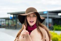 Le portrait en gros plan de la fille dans un chapeau brun et un oeil beige de manteau cligne de l'oeil à l'appareil-photo, dirige Images stock