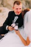 Le portrait en gros plan de la tristesse tenant le verre de vin tout en se reposant près de la jeune mariée Images libres de droits