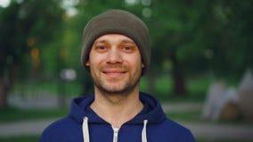 Le portrait en gros plan de mouvement lent du jeune homme attirant dans les sports vêtx le chapeau et la veste regardant l'appare banque de vidéos