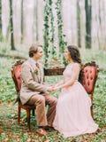 Le portrait en gros plan de se tenir remet des nouveaux mariés et se reposer sur les chaises molles élégantes entre le tronçon ac Image stock