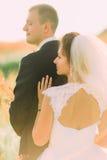 Le portrait en gros plan des épaules nues de la jeune mariée s'appuyant sur le marié dans le domaine de blé Photo libre de droits