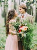 Le portrait en gros plan des nouveaux mariés regardant dans l'un l'autre des yeux La jeune mariée avec de longs cheveux bouclés t Photos stock