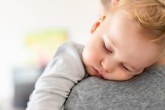 Le portrait en gros plan du gar?on caucasien blond adorable mignon d'enfant en bas ?ge dormant sur des p?res ?paulent ? l'int?rie images libres de droits