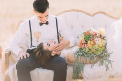 Le portrait en gros plan du marié choyant le visage du mensonge sur sa jeune mariée de recouvrements dans le domaine ensoleillé Photo libre de droits