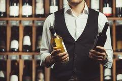 Le portrait en gros plan du sommelier tient une bouteille de vin rouge et blanc sur le fond de cave Variétés d'alcoolique images stock