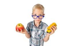 Le portrait en gros plan grand-angulaire du garçon un étudiant dans la chemise en verres étreignant la pomme et le schoolbus dans image stock