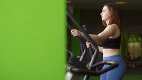 Le portrait en gros plan latéral de la femme modifiant la tonalité ses muscles sur l'entraîneur elliptique dans le centre de fitn banque de vidéos