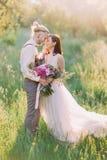 Le portrait en gros plan PF les nouveaux mariés en parc ensoleillé L'homme choie le café de sa jeune mariée Image libre de droits