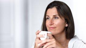 Le portrait en gros plan satisfacted la femme de sourire appréciant la tasse se tenante d'intérieur de porcelaine de thé ou de ca banque de vidéos