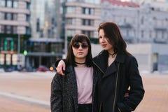 Le portrait extérieur de deux élégants et de belles filles a habillé des amies sur le fond de la ville Photographie stock libre de droits