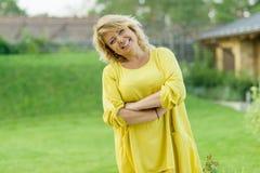 Le portrait extérieur de la femme d'une cinquantaine d'années mûre positive, femelle avec des bras a croisé, beau sourire, jardin image stock