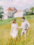 Le portrait extérieur des nouveaux mariés gais tenant des mains et marchant dans le domaine près du vieux château Photo libre de droits