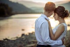 Le portrait extérieur romantique du charme juste a marié tendrement étreindre et apprécier le coucher du soleil sur la berge photo libre de droits