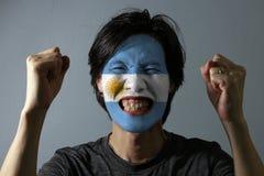 Le portrait gai d'un homme avec le drapeau de l'Argentine a peint sur son visage sur le fond gris photo stock