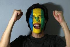 Le portrait gai d'un homme avec le drapeau de Saint Vincent a peint sur son visage sur le fond gris Le concept du sport ou du res image stock