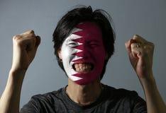 Le portrait gai d'un homme avec le drapeau du Qatar a peint sur son visage sur le fond gris photographie stock libre de droits