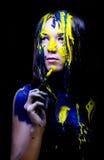 Le portrait haut étroit de beauté/mode de la femme a peint bleu et jaune avec les brosses et la peinture sur le fond noir Photographie stock libre de droits