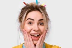 Le portrait haut étroit de la jeune femme étonnée heureuse souriant largement, tient des joues à la main La belle femelle entend  images stock