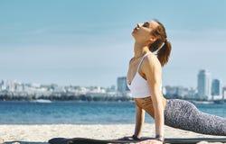 Le portrait haut étroit de la jeune femme sportive mince fait des exercices de yoga et l'étirage sur la plage de sable avec la vi photographie stock