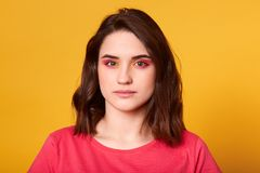Le portrait haut étroit de la jeune fille de brune avec lumineux composent regarder directement la caméra Paupières colorées dans photo libre de droits