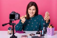 Le portrait haut étroit de la pose gaie de blogger de beauté d'isolement au-dessus du fond rose dans le studio, tenant la brosse  photographie stock