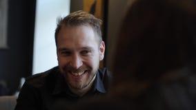 Le portrait haut étroit du jeune homme heureux boit du café, parle et sourit avec le hergirlfriend tout en se reposant au banque de vidéos