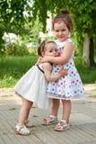 Le portrait heureux d'enfant, l'amour de deux filles et l'étreinte dans la ville se garent, le su Photographie stock