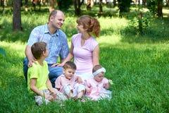 Le portrait heureux de famille sur extérieur, groupe de cinq personnes se reposent sur l'herbe en parc de ville, saison d'été, en Image stock