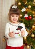 Le portrait heureux de fille dans la décoration de Noël, jouant avec le jouet de bonhomme de neige, concept de vacances d'hiver,  Photographie stock libre de droits