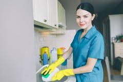 Le portrait horizontal de la fille lave des plats dans l'évier Elle est dans la cuisine Sourires et regards de brune sur l'appare photo libre de droits