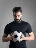 Le portrait intense du joueur de football tenant et regardant la boule s'est focalisé au-dessus du fond gris de studio photo stock