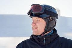 Le portrait latéral d'un homme dans un casque de ski et les lunettes de ski sur le fond d'un ski font du surf des neiges la desce Image libre de droits