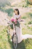 Le portrait latéral de la jeune mariée dans la longue robe blanche se tenant près du bycicle avec le bouquet de fleur en vert ens Images libres de droits