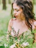 Le portrait latéral en gros plan de la femme avec de longs cheveux bouclés dans la robe rose-clair tenant le bouquet vert et blan Photographie stock