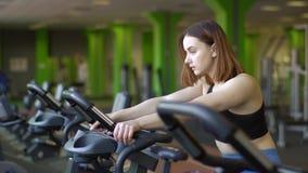 Le portrait latéral en gros plan de la femme modifiant la tonalité ses muscles sur le vélo d'exercice dans le gymnase vert banque de vidéos