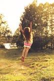 Le portrait modifié la tonalité de la petite fille mignonne danse en nature au coucher du soleil d'été Photos stock
