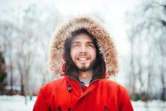Le portrait, plan rapproché d'un homme élégamment habillé de jeunes souriant avec une barbe s'est habillé dans une veste rouge d' Photo stock