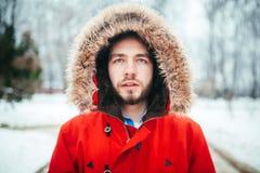 Le portrait, le plan rapproché d'un jeune homme élégant avec une barbe habillée dans une veste rouge d'hiver avec un capot et la  Image stock