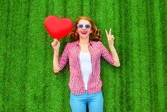 Le portrait rit la femme avec le rouge un ballon à air sous forme de coeur Photographie stock