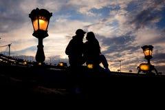 Le portrait romantique des couples affectueux silhouettent se reposer sur le pont à chaînes près du réverbère de foudre à Budapes Photos stock