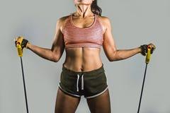 Le portrait sans visage de la femme d'ajustement de jeunes et de sport sportif travaillant dur avec la résistance élastique se ré image libre de droits